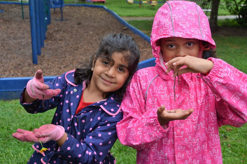 Two elementary girls holding earthworms on a rainy day