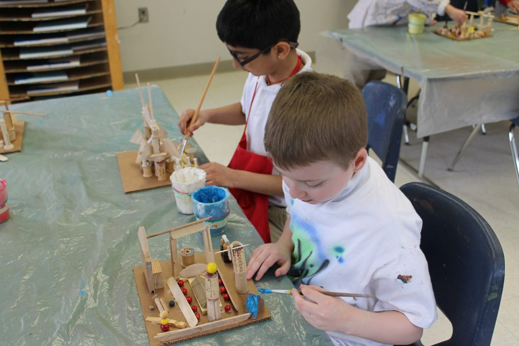 Elementary students painting their sculptures