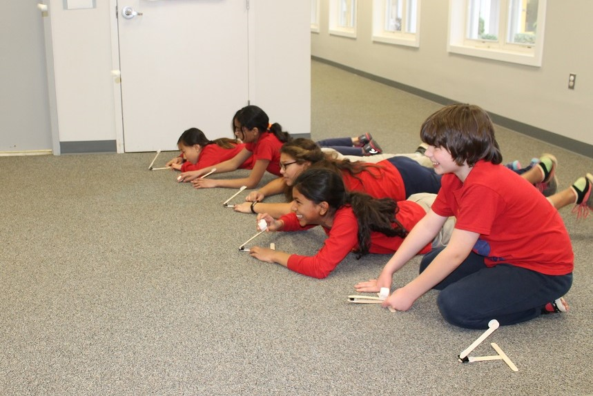 Elementary students utilizing catapults while learning about engineering
