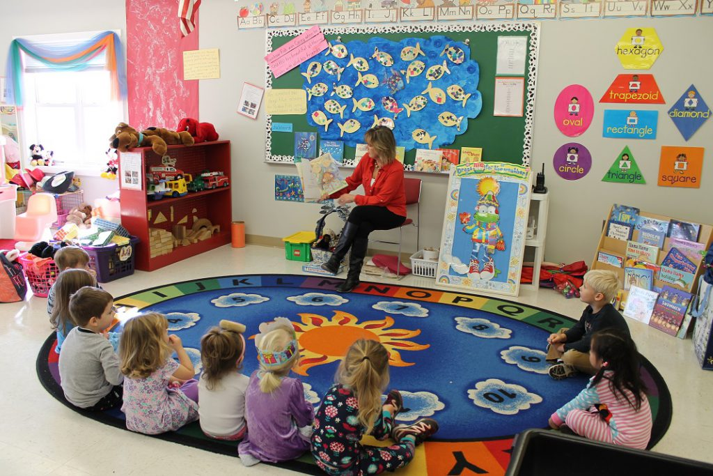 Preschool teacher reading to students during circle time
