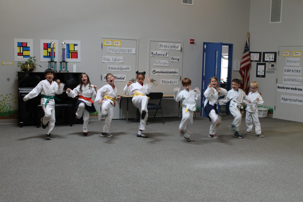 Elementary students in karate class doing jump kicks