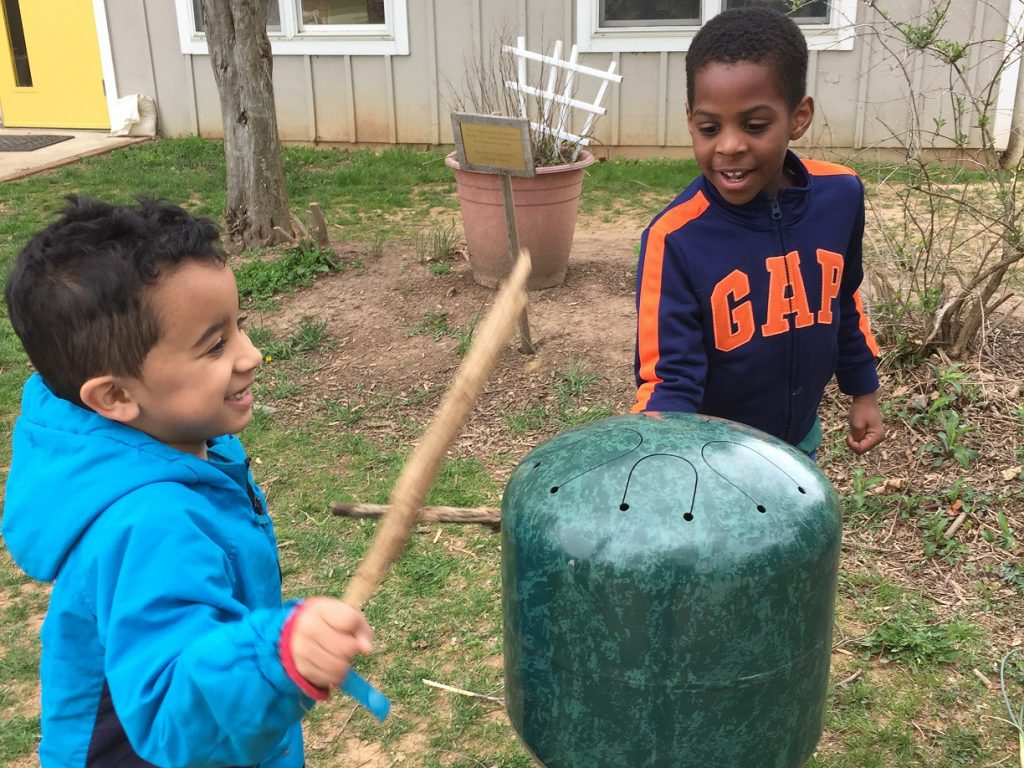 Preschool boys playing a drum outside