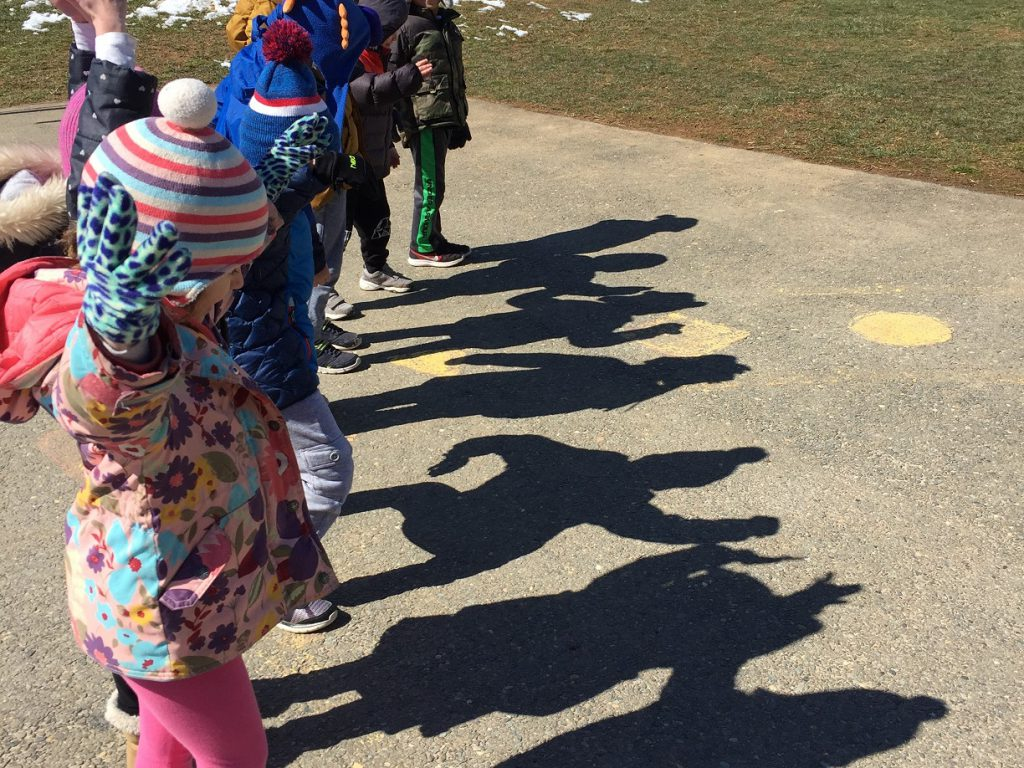 Preschool students watching their shadows as they dance