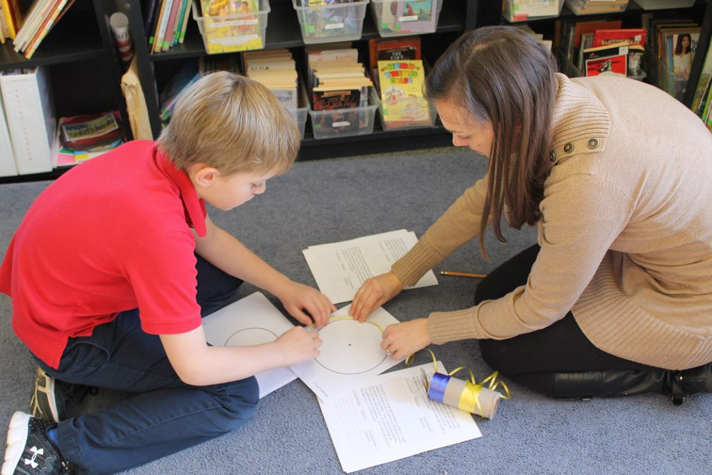Teacher assisting elementary student in determining pi with yarn