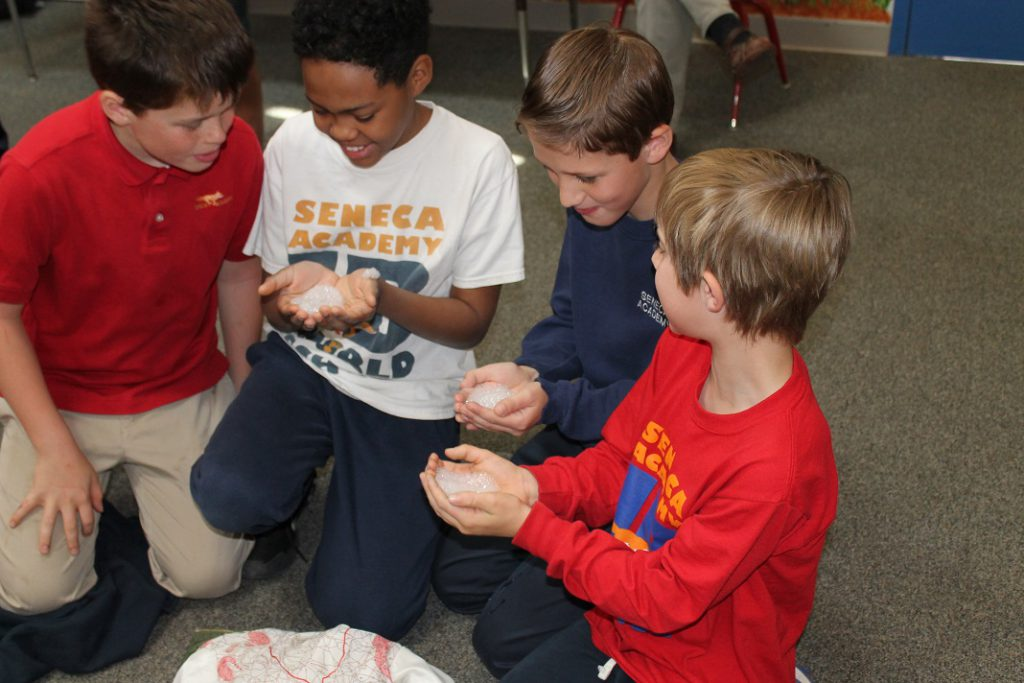 Four elementary boys doing science experiment with bubbles