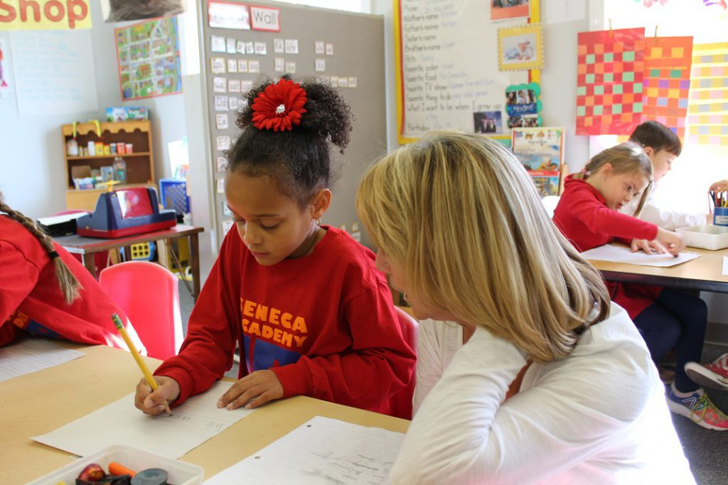 Teacher assisting elementary girl with handwriting