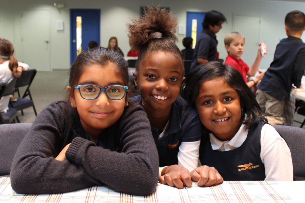 Three elementary girls smiling