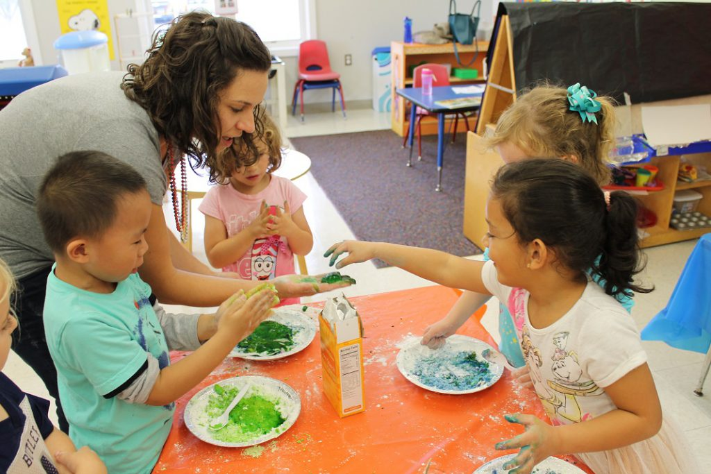 Preschool students doing slime science experiment with teacher
