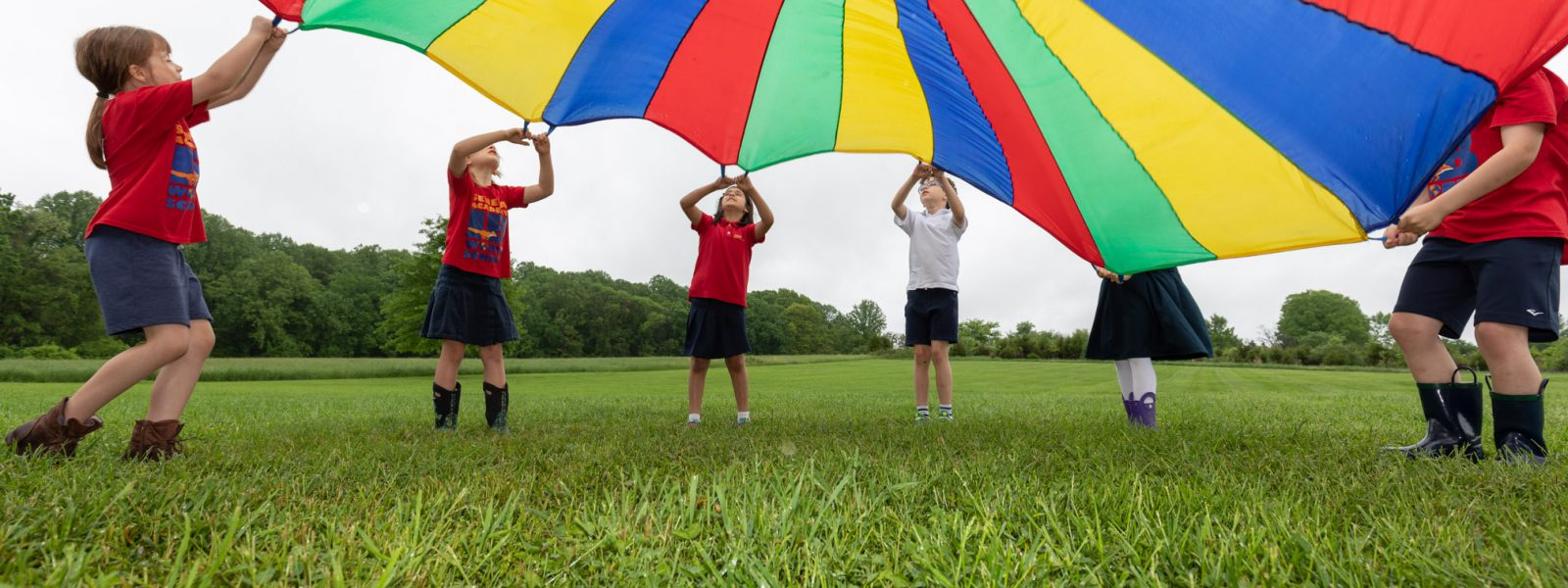 Elementary students playing with a parachute outside