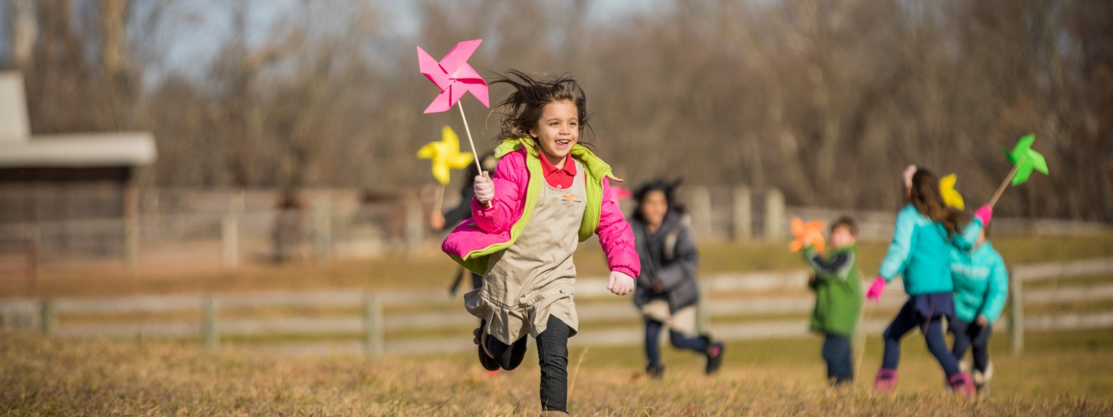 Elementary student running in field with pinwheel