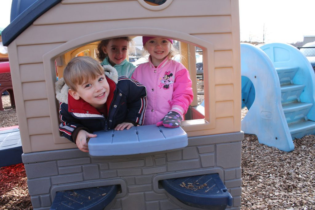 Preschool students in a play house outside