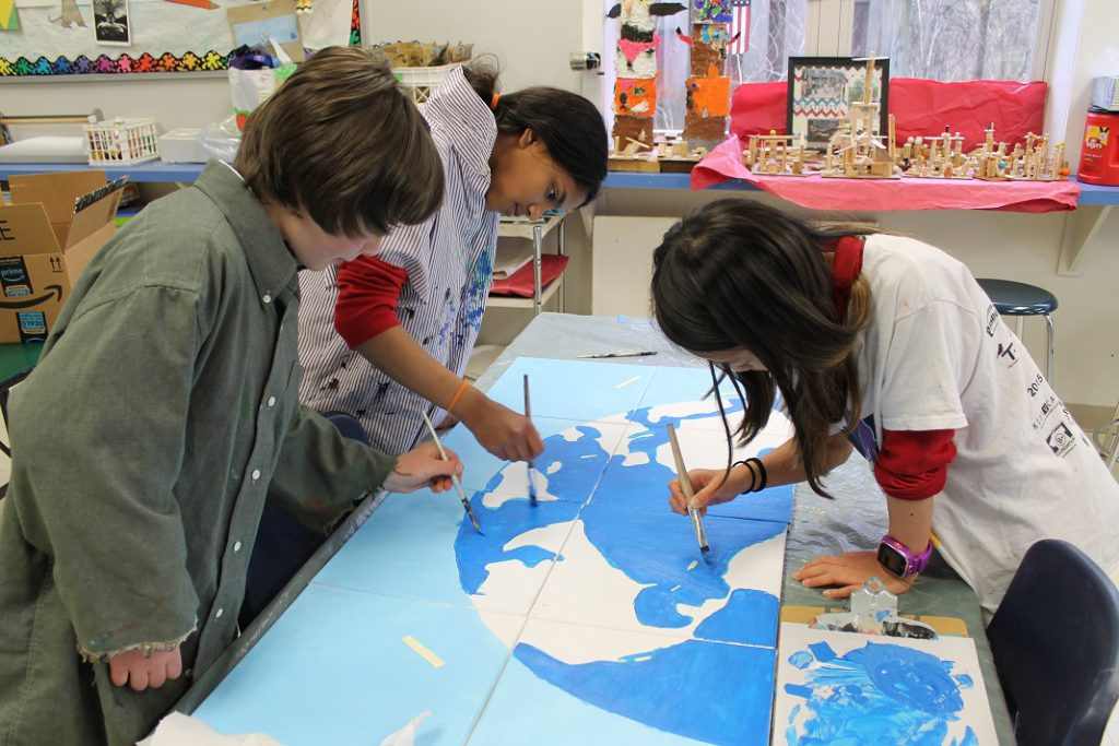 Elementary students painting a map of the world