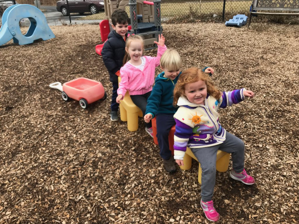 Preschool students making a pretend train with chairs on the playground