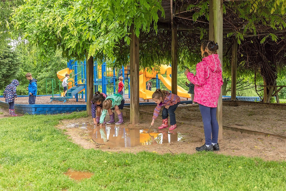 Elementary students playing outside in the rain